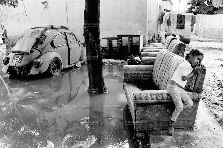 Mozambique. Province of Gaza. Chokwe. The Limpopo river has flooded the whole town. The family's furnitures are left outside the house to dry. A young girl sits on a sofa while an old Volkswagen (VW) beetle car has still its wheels in the water. © 2000 Didier Ruef