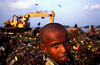 Twelve year old Kamal stands in front of a hydraulic digger on the Kajla rubbish dump where he is a professional scavenger.  He has never been to school, but earns his money by selling waste paper and plastic bags which he finds amongst the rubbish.  It is one of three landfill sites in this city of twelve million people.   Around 5,000 tonnes of garbage are dumped here each day and over a thousand people work among the rubbish, sorting through the waste and collecting items to sell to retailers for recycling.