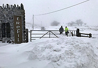 WEATHER PICTURE WALES<br /> Pictured: Two men walk through the heavy snow in the village of Trfil, south Wales, UK.<br /> Re: Beast from the East and Storm Emma has been affecting most parts of the UK.