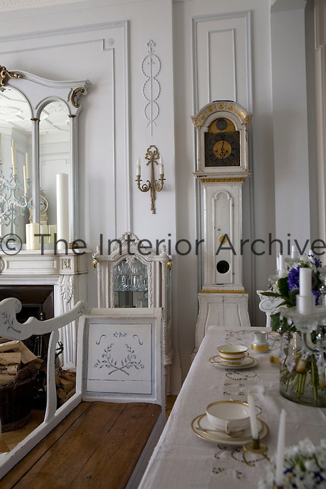 View over the dining table and settle in the living room towards a grandfather clock standing against the wood panelled wall