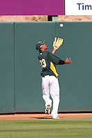Michael Taylor #23 of the Oakland Athletics chases a fly ball for an out against the Cleveland Indians in a spring training game at Phoenix Municipal Stadium on March 2, 2011  in Phoenix, Arizona. .Photo by:  Bill Mitchell/Four Seam Images.