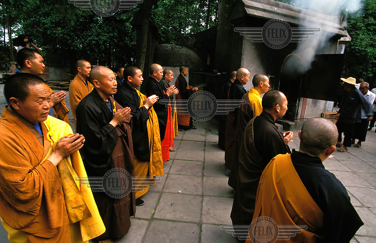 ©Mark Henley/Panos Pictures..China, Sichuan, Chengdu, Xindu..Return of religious values. Monks praying during Buddhist funeral cremation ceremony at Baoguang Si (Monastery of Divine Light).