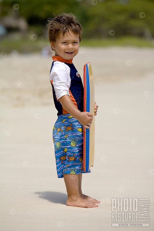 A two-year-old boy holds a body board at Kailua Beach, Oahu, Hawaii.