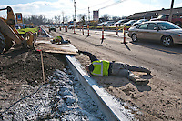 A supervisor lays on the ground to check the level of fill dirt used to build temporary ramps as a sheet of steel is laid for the ramp into a shopping center after new concrete curbs were laid on Westerville Road at Dempsey as roadway improvements near completion at the intersection.The changes are part of an improvement project at the I-270 interchange to upgrade the entrance road to Westerville, OH.