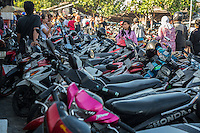 Jimbaran, Bali, Indonesia.  Motorbikes Parked outside Entrance to Fish Market.