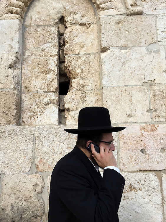 """5. """"Hasid (ultra-orthodox Jew) on Cell Phone"""":  outside walls of the Old City, Jerusalem.<br /> <br /> At last we arrived in Jerusalem: the holiest city in the Holy Land. A Hasidic ultra-orthodox family was walking past the Old City's stone walls; father (the patriarch) on a cell phone, wife and sons at his side.<br />  <br /> According to Marc Rosenstein, an Israeli historian who is currently writing about my photographs, """"The dissonance between the 'heavenly' and the 'earthly' Jerusalem"""" is perhaps the most pervasive of the oppositions that characterize Israel today. The issue, as Marc (and I) see it, is that there is an undeniable contradiction between what Jewish liturgy calls """"the first flowering of our redemption,"""" and """"the presence of urban blight, pollution, corruption -- or even just of people going about their normal, quotidian, unmessianic lives...."""" This """"compels attention,"""" writes Marc. And I agree, having come to Israel on a spiritual quest to honor my parents, and now encountering so much more."""