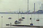 Thames estuary Thurrock Essex England 1990s. A weekend sailor the river The Dartford bridge is in the distance 1991
