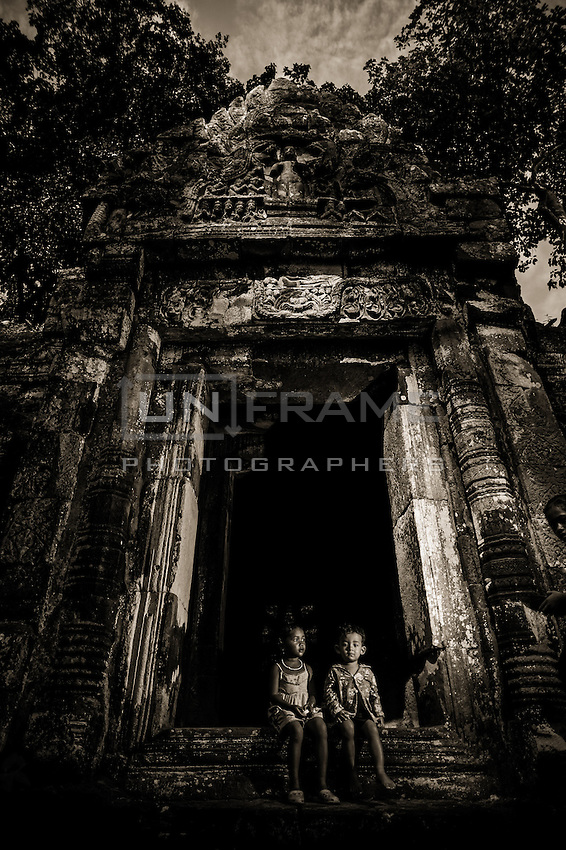 UNESCO World Heritage Site,  Ankgor wat temples . A couple of children sits in front of the monumntal entrace of a tall temple. Local children usually make their living by selling crafts and other products to tourists.   Seam Reap, Cambodia.