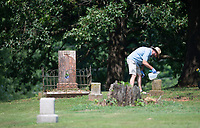 Gregg McGee of Farmington cleans a headstone Tuesday July 20, 2021at Oaks Cemetery which is located just south of the National Cemetery in Fayetteville. Many of the black citizens who lived and died in Fayetteville in the decades after the Civil War are buried in Oaks Cemetery. The Oaks Cemetery Group was formed in 2009 to reclaim the cemetery from the weeds and grass. Established in 1867, the cemetery is on the Arkansas Register of Historic Places. Visit nwaonline.com/21000721Daily/ and nwadg.com/photo. (NWA Democrat-Gazette/J.T. Wampler)