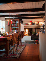 A fire blazes in the kitchen hearth, with glowing candles on the mantelpiece and the Swedish wrought iron chandelier