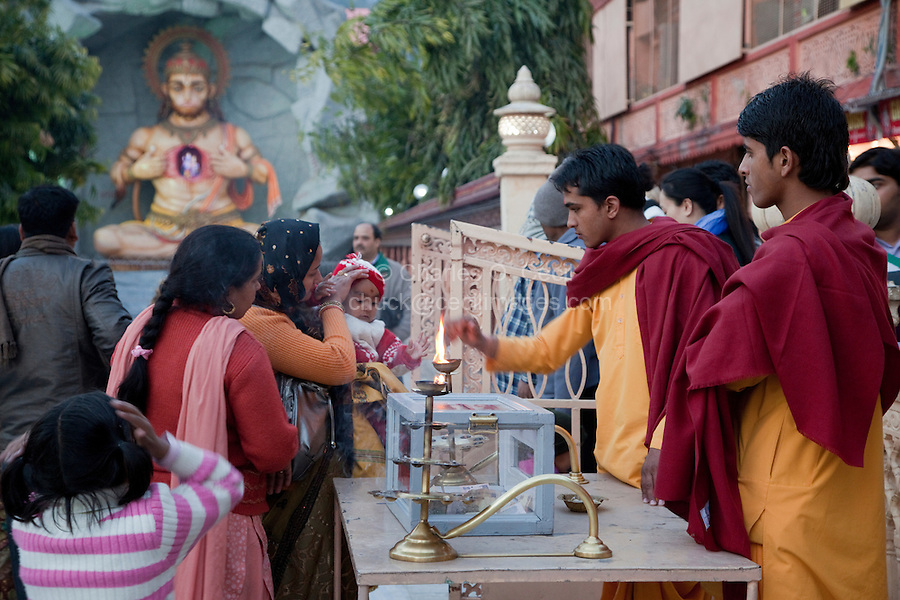 India, Rishikesh.  Monk Giving Blessing to Baby  after Evening Prayer (Aarti) at the Parmarth Niketan Ashram.  Hanuman Shrine in Background.