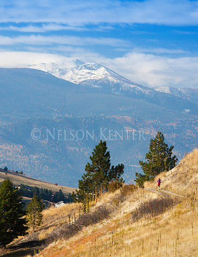 Runners use a trail along the south side of Mount Sentinel in Missoula, Montana. Snow covered Lolo Peak in the Bitterroot Mountains in the distance
