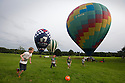 07/06/16<br /> <br /> Childen play football in the park as the balloons prepare for take off.<br /> <br /> After weeks of rain the Nottingham and Derby Hot Air Balloon Club finally get to launch their three hot air balloons from Allestree Park, Derby.