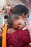A young child with bright orange tilak on her forehead<br /> sleeps on her mothers shoulder.