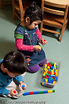 Educaton preschool  3-4 year olds boy and girl playing side by side with colorful connecting blocks vertical