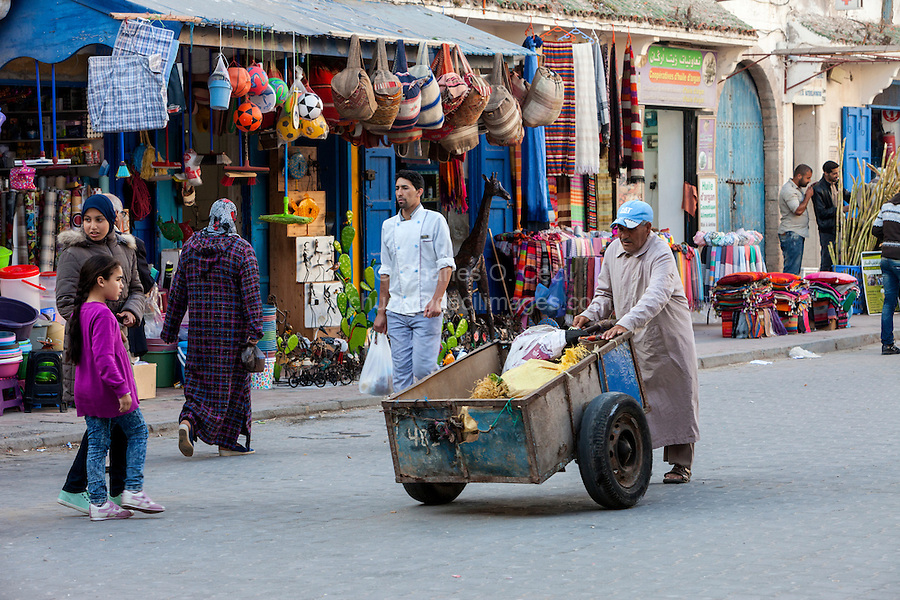 Essaouira, Morocco.  Porter Pushing Cart with Shopper's Purchases in Avenue de l'Istiqlal.