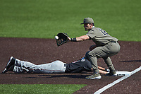 Dominic Keegan (12) of the Vanderbilt Commodores waits for a pick-off throw as Braylen Wimmer (3) of the South Carolina Gamecocks dives back into first base at Hawkins Field on March 21, 2021 in Nashville, Tennessee. (Brian Westerholt/Four Seam Images)