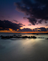 A camera's slow shutter speed flattens out the ocean's waves to create a calming sunset view of Kohanaiki Beach Park (a.k.a. Pine Trees Beach), Big Island.