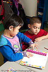 Education Elementary school Grade 1 mathematics manipulatives and hands on activities boy and girl counting colored connecting cubes vertical