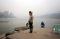 CHINA. Sichuan Province. Chongqing. A woman stands on the banks of the Yangtze river which is at its lowest for the past 150 years as a result of a nationwide drought. Chongqing is a city of over 3,000,000 people, famed for being the capital of China between 1938 and 1946 during World War II. It is situated on the banks of the Yangtze river, China's longest river and the third longest in the world. Originating in Tibet, the river flows for 3,964 miles (6,380km) through central China into the East China Sea at Shanghai.  2008.