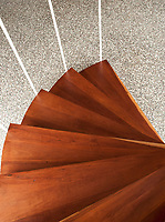 Detail of a wooden spiral staircase and terrazzo floor