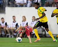 NASHVILLE, TN - JULY 3: Paul Arriola #7 goes down after a tackle by Elvis Powell #5 during a game between Jamaica and USMNT at Nissan Stadium on July 3, 2019 in Nashville, Tennessee.
