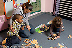 Educaton preschool 4-5 year olds female volunteer student teacher working with children on puzzle activity horizontal sitting with arm around sad boy