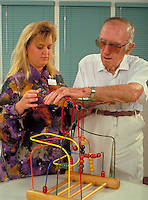 female physical therapist working with elderly male rehabilitation patient. ocupations, medical care.