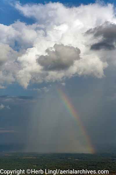 aerial photograph of a rainbow and rain pouring from cumulonimbus cloud in Alabama