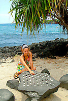 Young woman playing konane, Hawaiian checkers, at Puu honua honaunau or commonly known as City of refuge, a national historical park south of Kona on the big island.