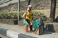 A street sweeper/cleaner, using home made utensils like old and modified Luggage Roller case and a modified home made scoop. Photography life on the streets, in Manila, Philippines