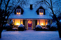 Exterior of house at dusk with Christmas lights on.