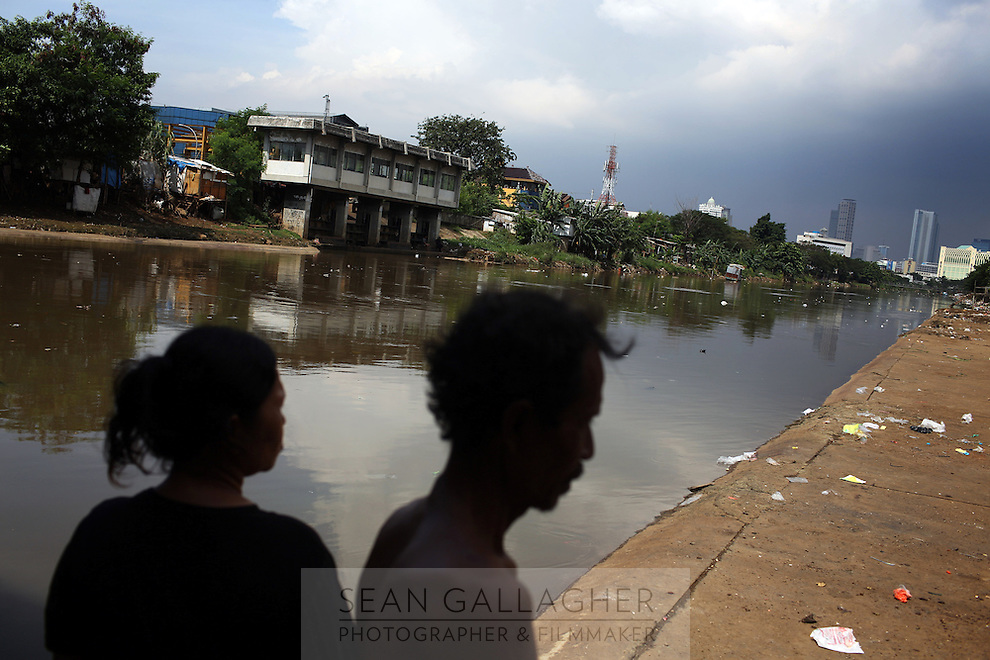 """Rain clouds gather over Jakarta's central business district, as two of the city's slum resents look over one of the canals that were built to help deal with floods. According to the Jakarta Globe """"Indonesia has been experiencing its most extreme weather conditions in recorded history…All regions across the archipelago have been experiencing abnormal and often catastrophic weather."""""""