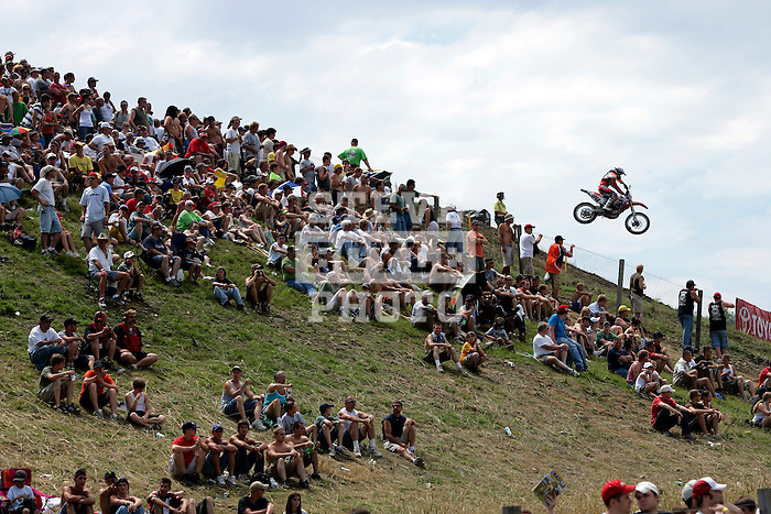 A rider comes off of the hill in front of fans while on the course at the Unadilla Valley Sports Center in New Berlin, New York on July 16, 2006, during the AMA Toyota Motocross Championship.