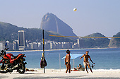 Rio de Janeiro, Brazil. Young men playing volleyball on Copacabana beach with the Sugar Loaf behind and a red motorbike.