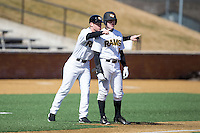 VCU Rams third base coach Kurt Elbin (6) goes over the Georgetown Hoyas defense with James Bunn (1) at Wake Forest Baseball Park on February 13, 2015 in Winston-Salem, North Carolina.  The Rams defeated the Hoyas 6-3.  (Brian Westerholt/Four Seam Images)