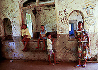 Children inside old Japanese World War II grafitti covered hospital, now used for storage in copra production in Truk Micronesia.