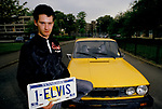 'ELVIS FANS', CHRIS CONSTABLE STANDING IN THE STREET BESIDE HIS BRIGHT YELLOW CAR HOLDING HIS AMERICAN '1 ELVIS' CAR NUMBER PLATE, SOUTH LONDON