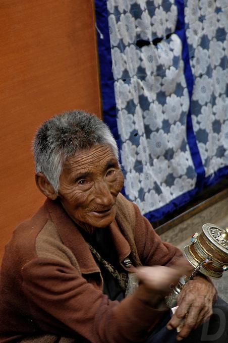 A tibetan with his Prayer wheel in the side street of Lhasa, near Barkhor street,Tibet