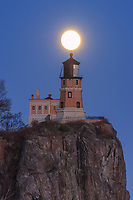 """""""Super Moon over Split Rock Lighthouse""""<br /> <br /> The December (near) full Cold Moon rose through a pastel palette on the eve of the Supermoon. Split Rock Lighthouse and Lake Superior helped paint a serene scene for the event. As it gained altitude, the moon glowed perfectly above the lens of the lighthouse."""