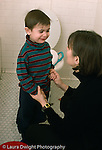 Boy, 3 years old toilet training resistant, with mother, crying in bathroom at home vertical