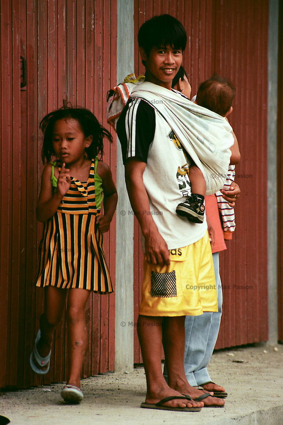 A girl runs past a family waiting for a bus in one of the hamlets in the Philippine Cordillera at the northeastern part of main island of Luzon, Philippines. Kiangan, Ifugao. June, 2000