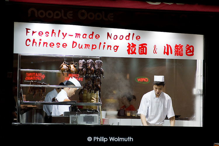 A cook prepares food in the window of a Chinese takeaway noodle and dumpling restaurant in Oxford Street, London.