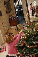 Mother and daughter (5-7) decorating Christmas tree, reflection in mirror (Licence this image exclusively with Getty: http://www.gettyimages.com/detail/73532510 )
