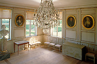 Gilt-framed oval ancestral portraits hang on the panelled walls of this salon, red gingham blinds dress the windows and a crystal chandelier hangs from the ceiling