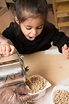 Education Preschool 3 year olds girl pouring own milk into cereal container
