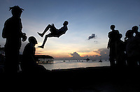 Boys take turns jumping over the harbor wall into the water below in Stone Town in Zanzibar, Tanzania.