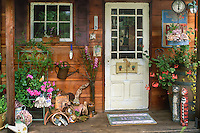 Old salvaged door entry to rustic country garden potting shed decorated with bric-a-brac and flea market finds