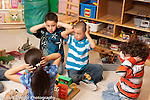 Education preschool 4-5 year olds holding hands over ears in coordinated game after setting up toy furniture