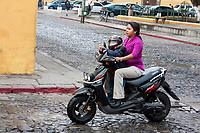 Antigua, Guatemala.  Boy with Lollipop and Helmet on Motorbike with Mother.